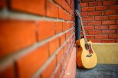 Brown guitar with red brick wall.