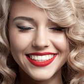 Close up face of beautiful Woman. Healthy Curly Hair. Gorgeous smile.