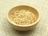 Wooden Bowl With Roasted Chopped Hazelnuts On Rattan Underlay
