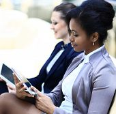 Businesswomen With Digital Tablet Sitting on sofa and working In Modern Office