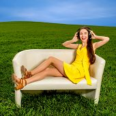 Young Girl Listening And Enjoying To The Music On The Couch In The Green Field