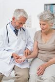 Male doctor taking a senior females pulse at the medical office