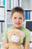 Portrait of little boy with teddy bear in clinic