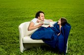 Man Take Care About His Girlfriend On The Couch On The Green Field