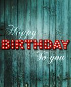 Shabby chic wooden background with glowing letters writing Happy Birthday to you