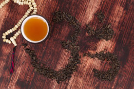 foto of ohm  - Cup of tea dry tea leaves forming ohm symbol and buddhist necklace - JPG