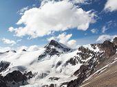 stock photo of aconcagua  - Snow covered mountain peak with big white cloud against dark blue sky - JPG