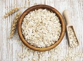 stock photo of oats  - Bowl of oats on a old wooden background - JPG