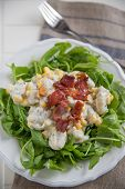 Gnocchi with cheese sauce, bacon and arugula