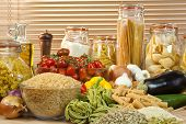 pic of healthy food  - A display of healthy foods including various vegetables jars of pasta rice seeds onions garlic olive oil aubergine tomatoes peppers spaghetti and courgettes - JPG