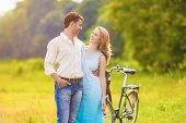 Caucasian Couple Walking Together In The Park Outdoors With Bike.