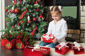 Happy Little Girl Open A Red Gift Box Near Christmas Tree