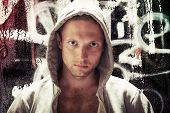 Young Caucasian Man In Hood, Street Artist Portrait With Grungy Graffiti Wall On Background, Toned E