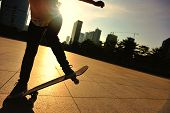 stock photo of skateboarding  - young woman skateboarder skateboarding at sunrise city - JPG