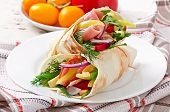 Fresh tortilla wraps with meat and vegetables on plate
