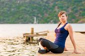 Young Brunette Sitting On A Pier In The Lotus Position