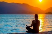 Girl In Lotus Position Admiring The Rising Sun
