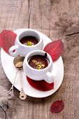 flavored hot chocolate in small ceramic chashkahna wooden table with red fallen autumn leaves