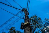 stock photo of utility pole  - An electric pole overcrowded with cables and a blue sky