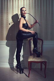 picture of latex woman  - Sexy woman in latex catsuit bite whip at vintage wall - JPG