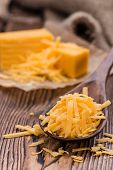 stock photo of grating  - Portion of grated Cheddar Cheese on rustic wooden background - JPG
