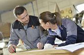Instructor with trainee in carpentry workshop