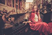 image of carnival ride  - Beautiful woman in red cloak riding on gondola - JPG