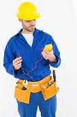 Repairman examining multimeter while standing against white background
