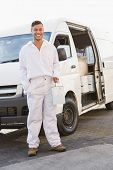 Painter smiling leaning against his van outside the warehouse