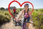 Active couple on a bike ride in the countryside against heart
