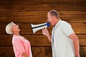 Man shouting at his partner through megaphone against overhead of wooden planks