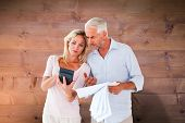 Anxious couple working out their bills against bleached wooden planks background