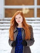 Young beautiful redhead woman in blue dress and grey coat at winter outdoors