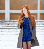 Young cute redhead woman in blue dress and grey coat at winter outdoors