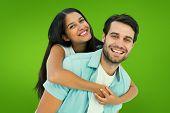 Happy casual man giving pretty girlfriend piggy back against green vignette
