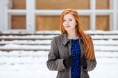 Closeup portrait of young beautiful redhead lady in blue dress and grey coat