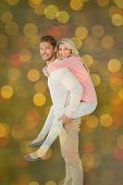 Handsome man giving piggy back to his girlfriend against close up of christmas lights