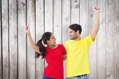 Excited couple cheering in red and yellow tshirts against wooden planks