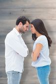 Angry couple facing off after argument against pale grey wooden planks