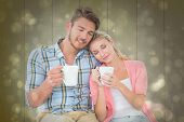 Attractive young couple sitting holding mugs against black abstract light spot design