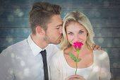 Handsome man kissing girlfriend on cheek holding a rose against black abstract light spot design
