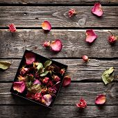 Rose petals inside open gift box and scattered on old vintage wooden plates. Sweet holiday background with rose petals.