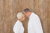 Angry older couple arguing with each other against wooden planks