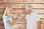 Unhappy couple having an argument against wooden planks background