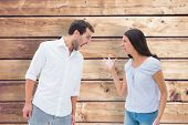 Angry couple shouting at each other against wooden planks background