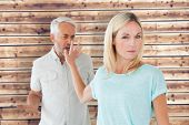 Woman not listening to her angry partner against wooden planks background