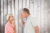 Older couple holding hands to mouth for silence against wooden planks