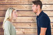 Childish couple having an argument against wooden planks background