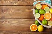 Citrus fruits in basket. Oranges, limes and lemons. Top view over wooden table background with copy space