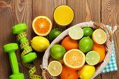 Citrus fruits in basket and dumbells. Oranges, limes and lemons. Over wood table background